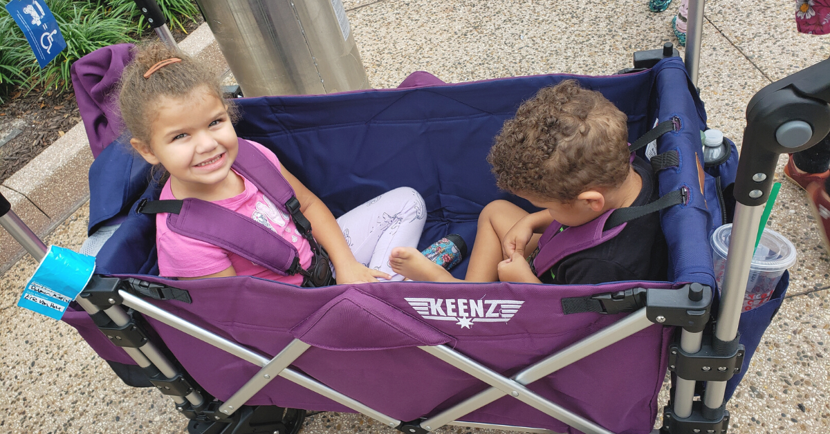 Two children inside a purple wagon stroller. The child on the left is a curly-haired girl with a pink shirt on, smiling at the camera. The child on the right is a curly-haired boy, looking down.
