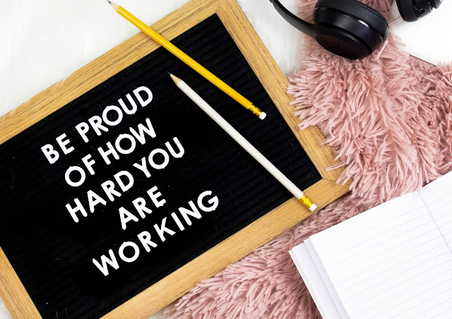 "A black sign which says ""be proud of how hard you are working"". The sign is in a flat lay and has pencils covering one of it's corners. There is also a camera and book in the photo."