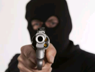 A masked armed robber with a revolver