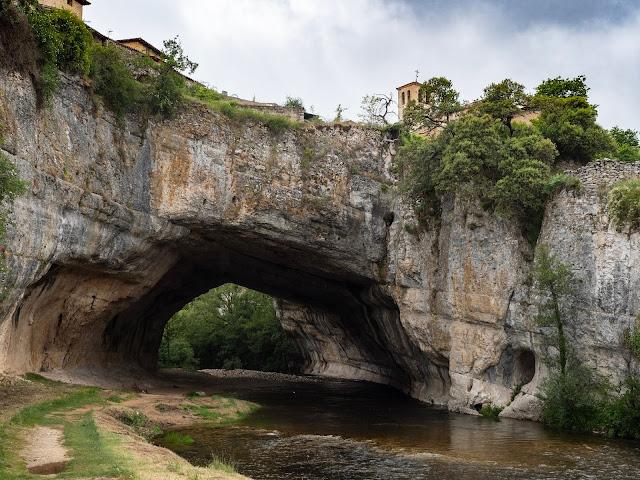Puente de piedra natural con las casas de Puentedey en lo alto