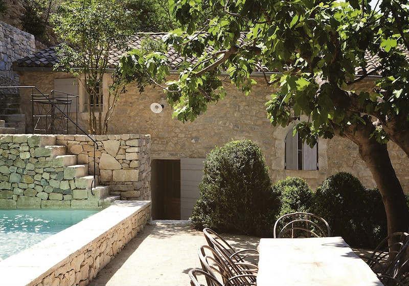 Patio de paredes de piedra con piscina
