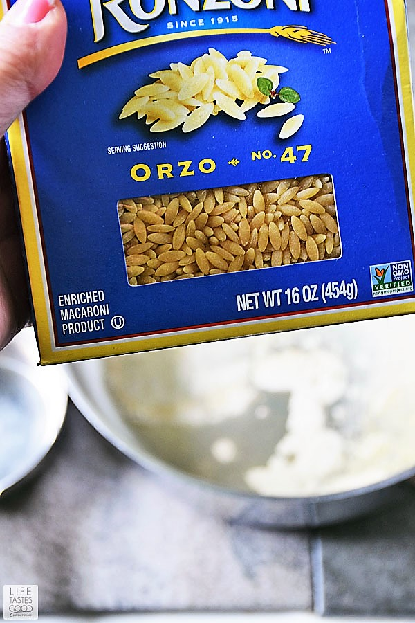Blue box of uncooked orzo pasta showing the size of the pasta grain and what to look for in the store when purchasing