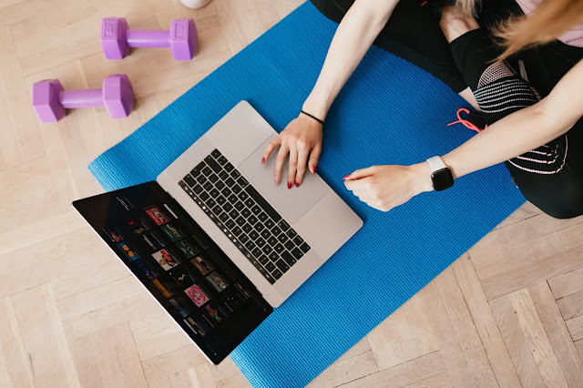 A girl using a laptop while sitting on a yoga mat with weights next to it