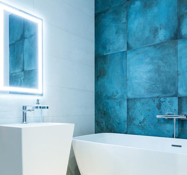 A fog-free, lit mirror in a white bathroom.