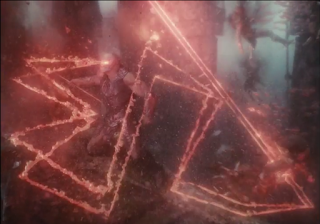 A shot of Darkseid, underwater, strangling one Atlantean while the twin red zigzagging beams of his Omega Effect seek out another.