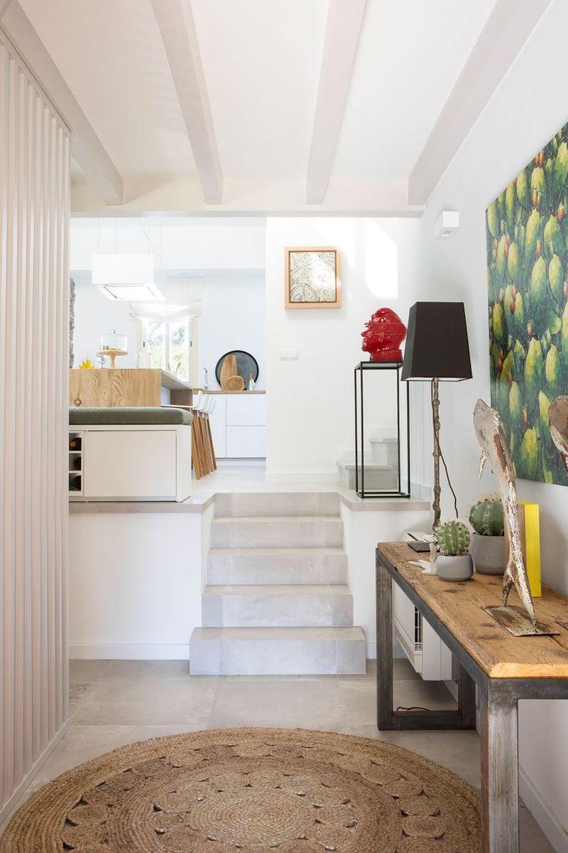 Acceso a la vivienda por hall con pared alistonada de madera
