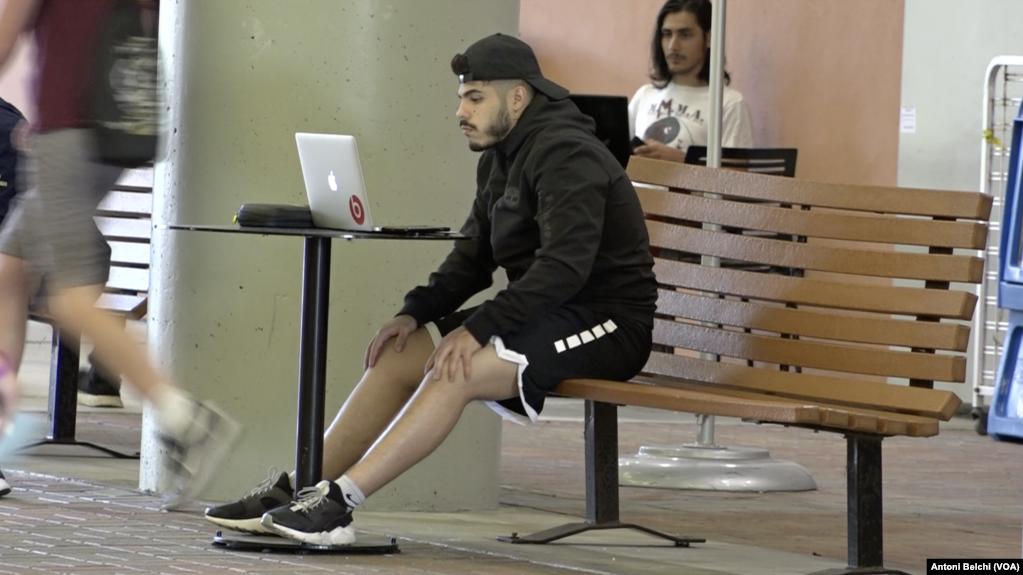 Un estudiante mirando su computadora personal en el campus de la Universidad Internacional de Florida en Miami (Florida), un día antes de que ordenaran su cierre completo / VOA