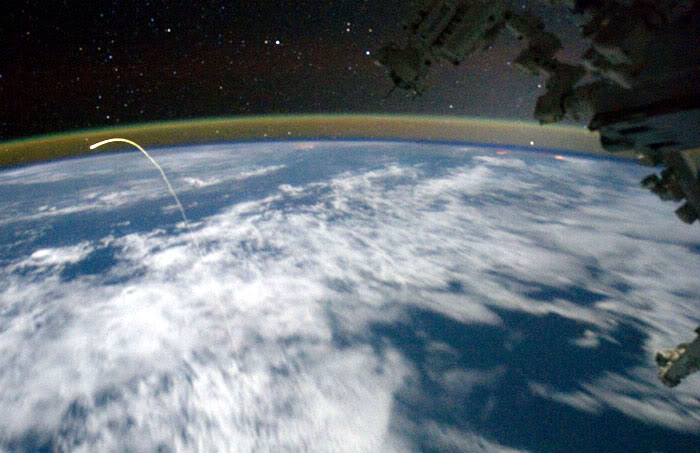 The plasma trail caused by space shuttle Atlantis as she re-entered Earth's atmosphere is photographed from the International Space Station's Cupola, on July 21, 2011.