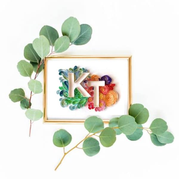 on-edge quilled monogram framed and hanging on wall surrounded by leafy branches