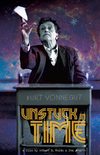 Vonnegut in black and white behind a lectern and infront of  a starscape