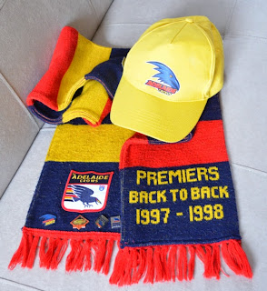 "A Crows scarf with a yellow peaked cap resting on top.  The cap has a Crows logo on the front.  The scarf has horizontal stripes in navy, red and yellow with red fringing at each end.  One end of the scarf has an Adelaide Crows patch stitched onto it with membership badges pinned along the bottom edge.  The other end of the double-sided scarf has the words ""Premiers back to back 1997–1998"" machine-knitted in fair isle."
