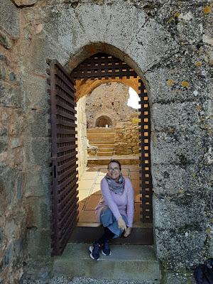 mulher sentada numa porta medieval