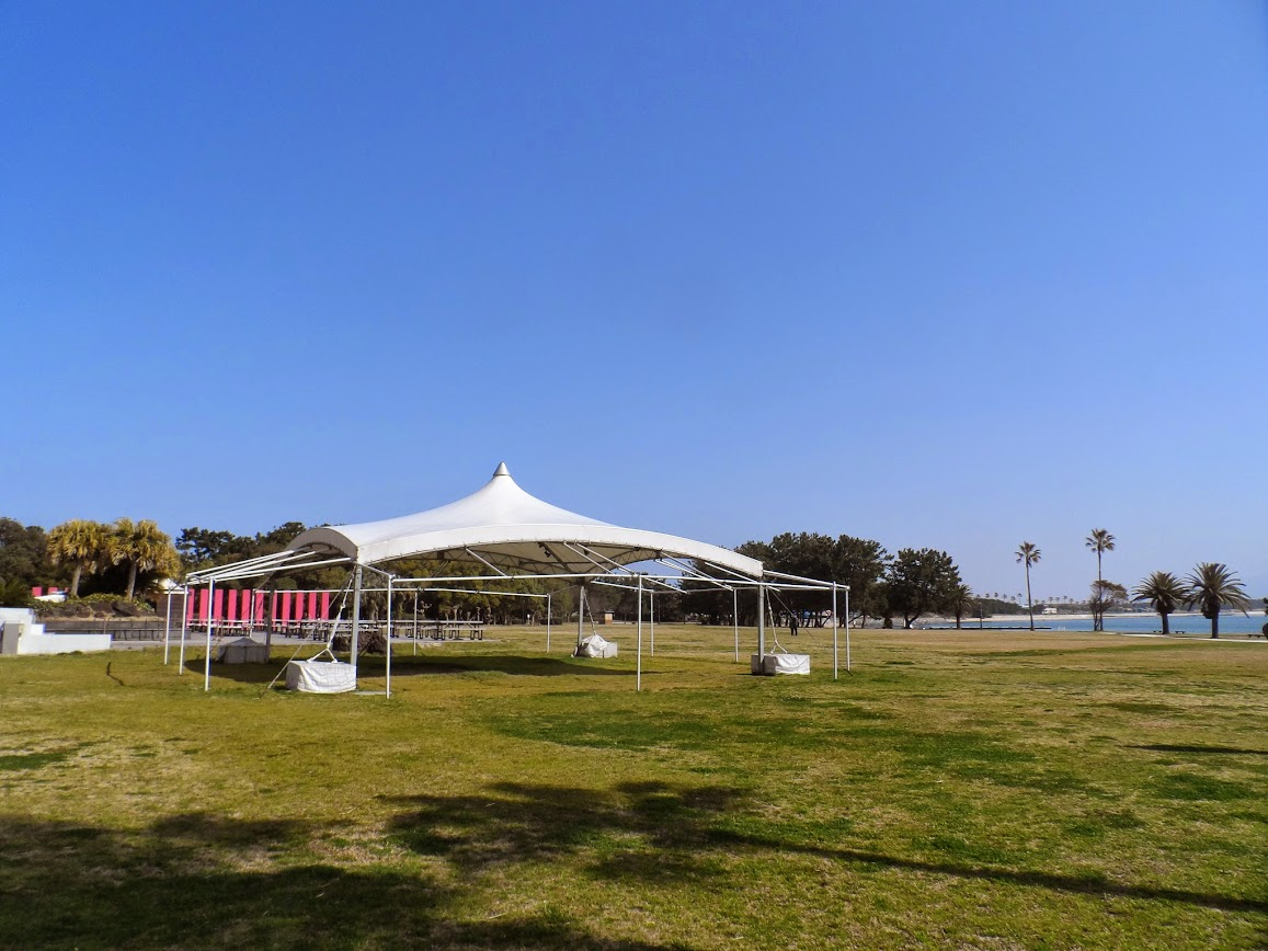 A white tent rises out of the fields beneath the cloudless sky