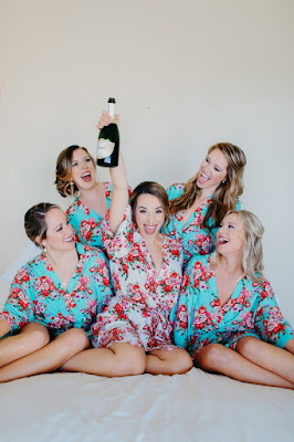 bridemaids in robes celebrating with champagne
