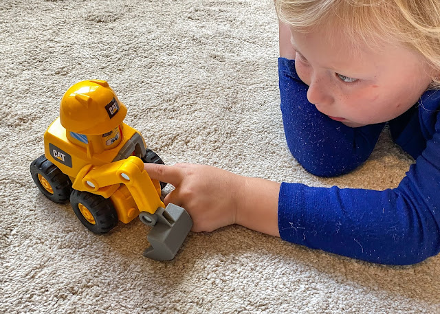 A 4 year old looking at a little cat construction digger toy