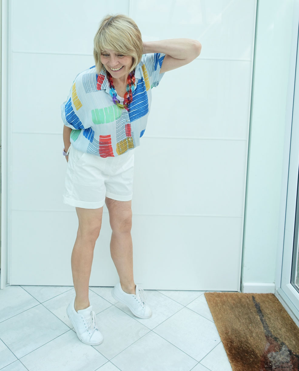 Gail Hanlon from over 50s style blog Is This Mutton in white shorts, abstract print blouse and white trainers