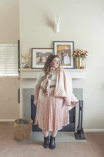 An outfit consisting of a pink peplum moto jacket, white and black striped 3/4 sleeve turtleneck top tucked into a pastel pink velvet skirt and black chelsea boots.