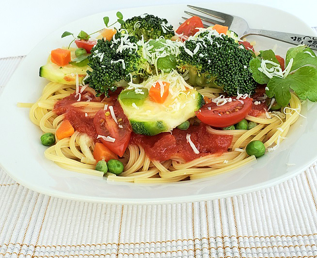 this is a bowl of spaghetti with fresh broccoli, peas, carrots and tomatoes on top