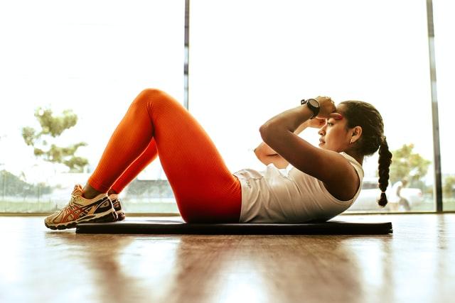 Mujer acostada sobre un mat de ejercicio frente a una ventana haciendo abdominales, vistiendo leggings color naranja y playera blanca