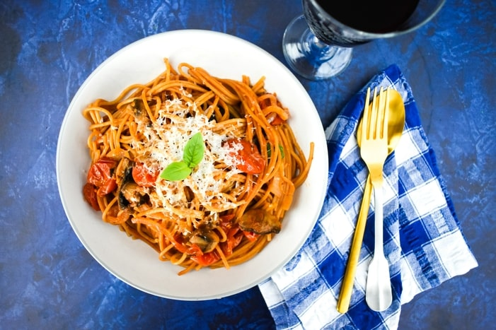 a bowl of mushroom and tomato spaghetti topped with grated vegan cheese and basil