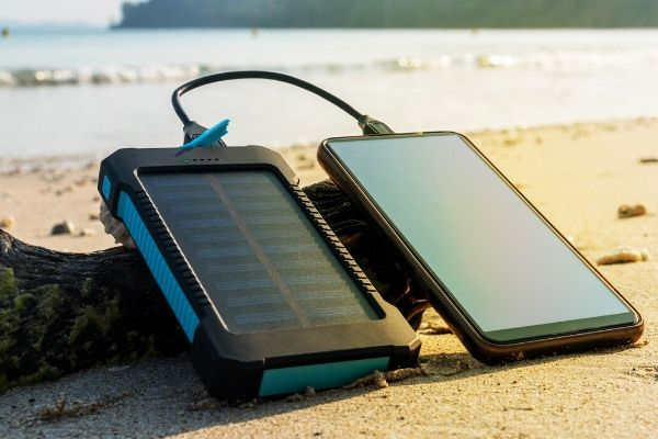 Solar phone charger charging iphone laying in the sun on the beach