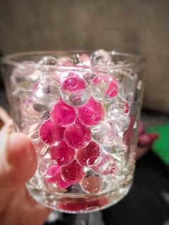 A glass with clear round orbs of water beads is held in someones hand to the camera. A blurred pink streak is visible through the beads. The background is blurred with a black ground base and a white wall