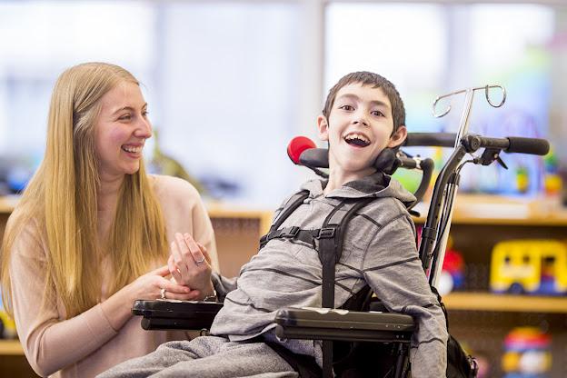 A imagem mostra um menino na cadeira de rodas sorindo e um terapeuta olhando e sorrindo para ele