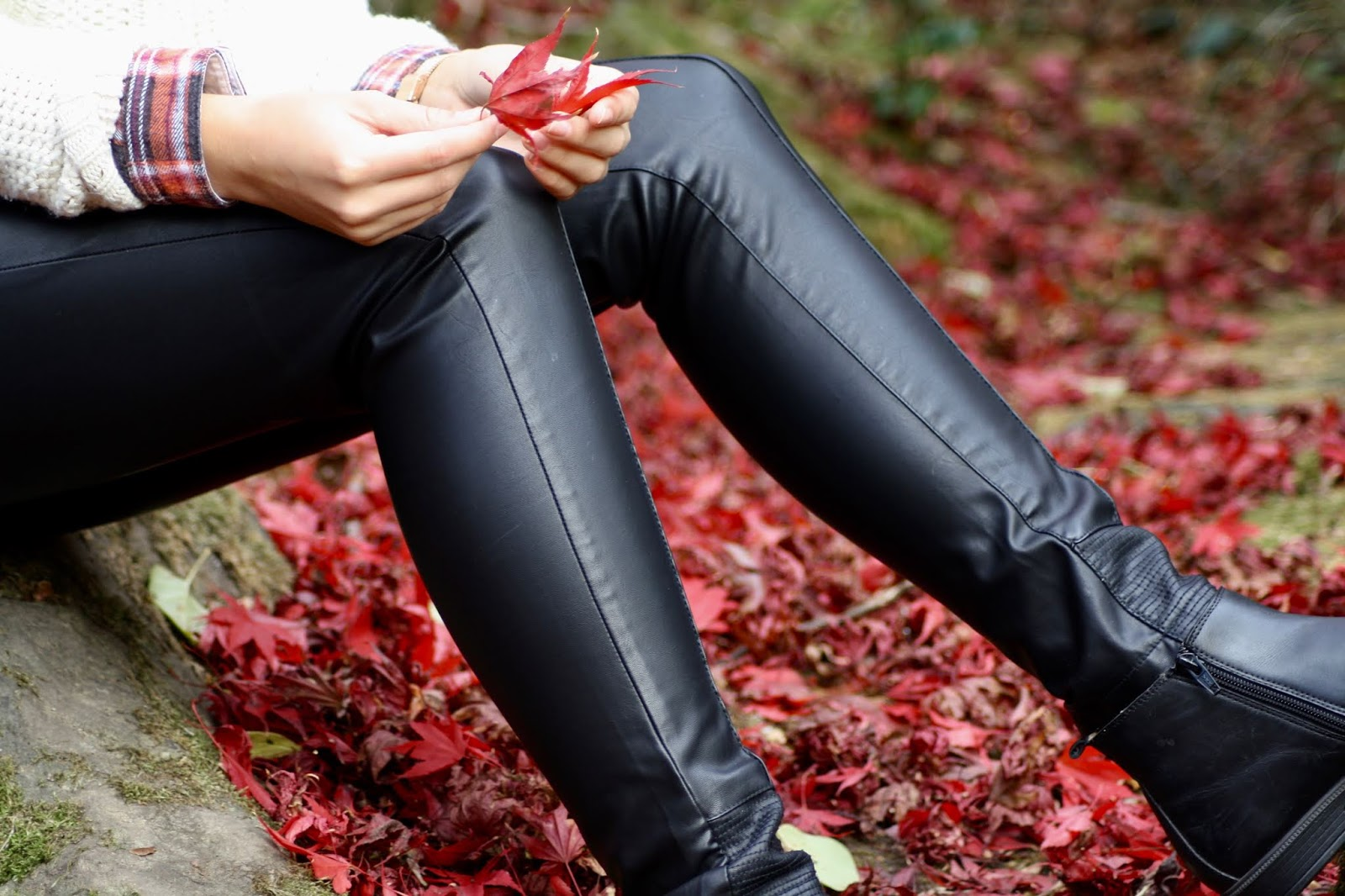 Abbey sits on a rock, holding a red leaf, details of faux leather trousers and cable knit jumper are visible