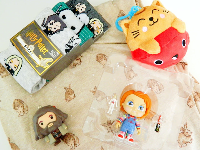a photo showing harry potter dark arts socks, a harry potter hagrid keyring, bunny pj pants, a cute cat plushie and a chucky horror figure