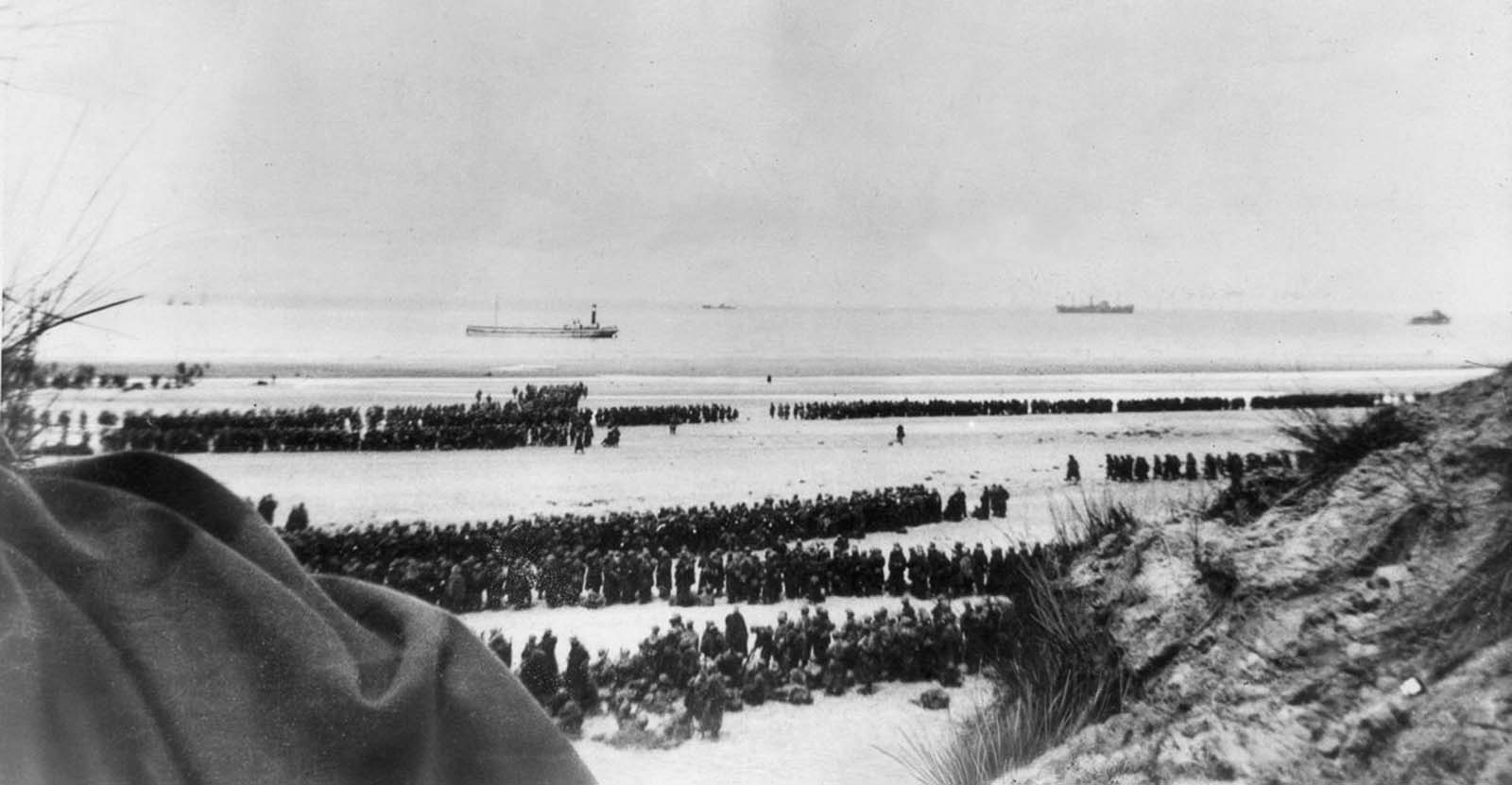 British and French troops await evacuation on the beach at Dunkirk.