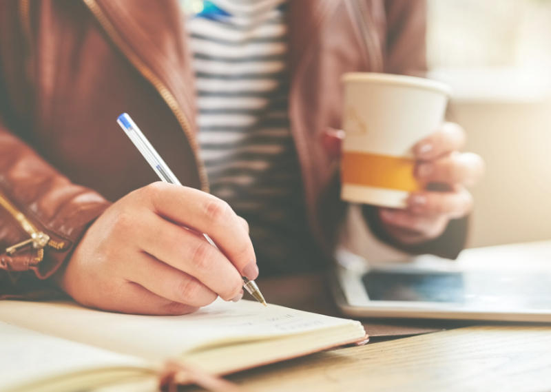 Somebody writing their thoughts in a journal in a blog post about 6 things you can do when you feel overwhelmed.