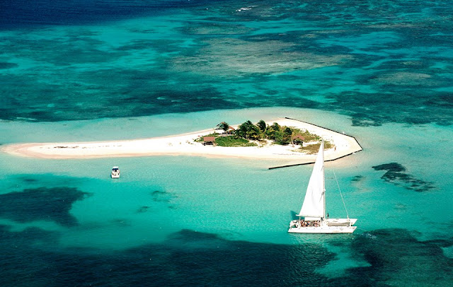 Ilet Caret , petit ilet au mileiu de l'océan avec catamaran - archipel de Guadeloupe