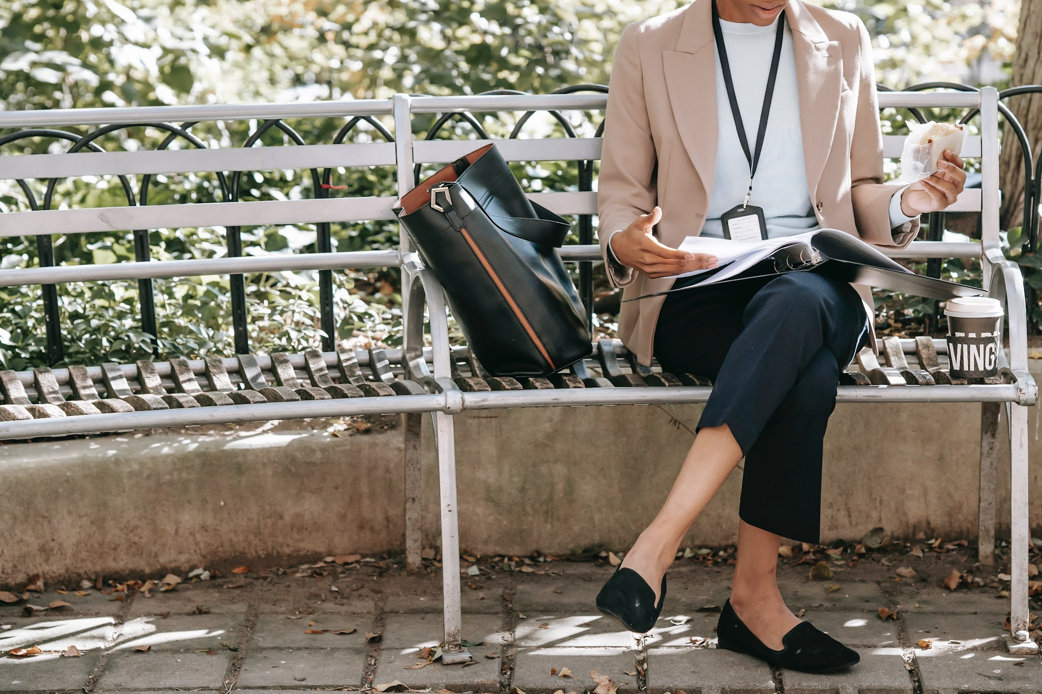 working woman sitting on a park bench reading and eating