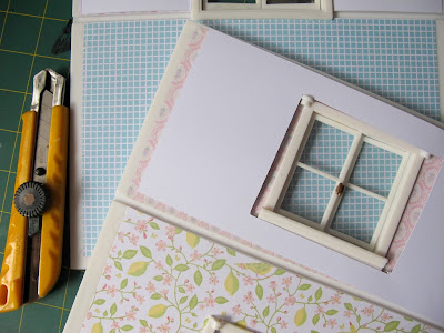 Cardboard template on top of a Lundby Smaland dolls' house wall with window, showing that it doesn't fit.