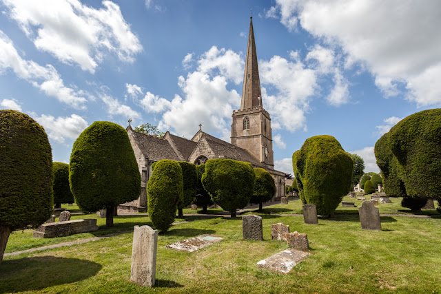 Sunshine of the yew trees and historic church of St. Mary's in Painswick