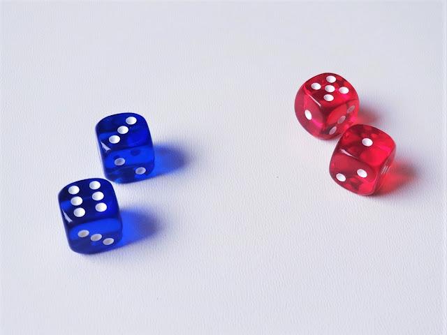 na zdjęciu znajdują się cztery kostki, dwie w kolorze niebieskim z wynikami sześć i trzy oraz dwie w kolorze czerwonym z wynikami pięć i jeden