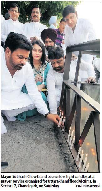 BJP leader and former MP Satya Pal Jain, Mayor Subhash Chawla and councillors light candles at a prayer service organised for Uttrakhand flood victims, in Sector 17, Chandigarh, on Saturday.