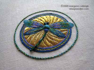 Completed embroidered dragonfly on top of underside couching in gold. Dragonfly is stitched in peacock colours: blues, greens, and purples. The tail is made up of beads and there are gold veins on the wings.