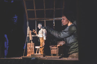 A Black puppeteer is holding a puppet that is painting at an easel, surrounded by furniture. A set piece of brown windows is in the background.