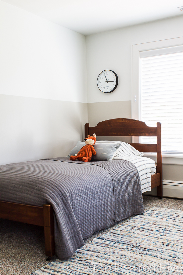 Boy's bedroom with antique bed, grey quilt, and blue pillow.