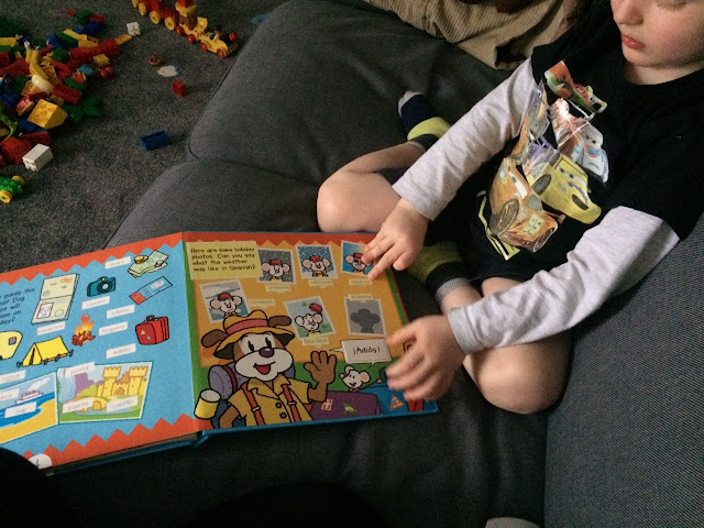 A child sitting on a sofa reading a book