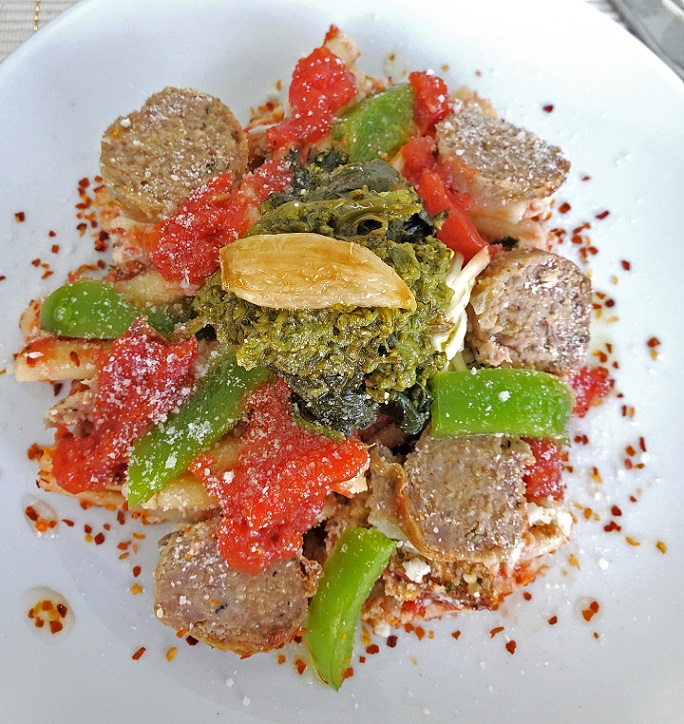 this is a dish of cavatelli pasta with sauce, sausage, peppers and broccoli rabe