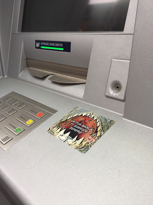 A sticker on an ATM that says the bank is always smiling at us. Really?