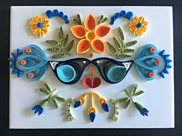 two quilled birds and blue, yellow, orange floral arrangement