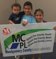 Three students holding a big MCPL library card.
