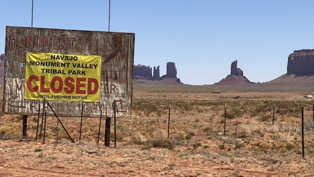 A big road sign for Monument Valley Tribal Park with a banner over it that says CLOSED