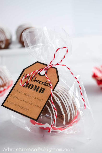 hot chocolate bomb packaged in cellophane with a printed tag tied with ribbon.