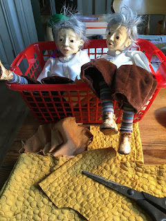 Two identical puppets sitting in a plastic basket, waiting for their clothing to be made partially dressed puppets for the Reflection puppet project in the making by Corina Duyn