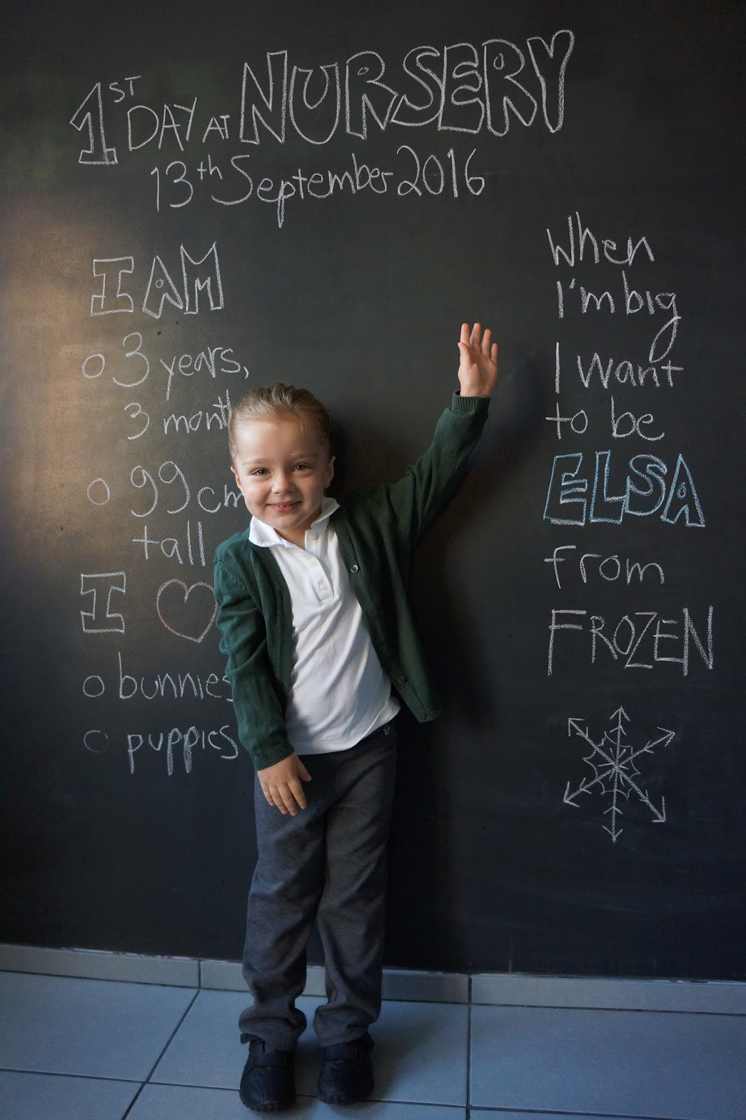 nursery child in front of black board art wall