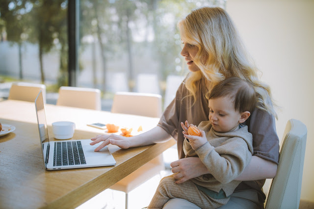 Work-from-home mom working on her laptop with toddler in her lap